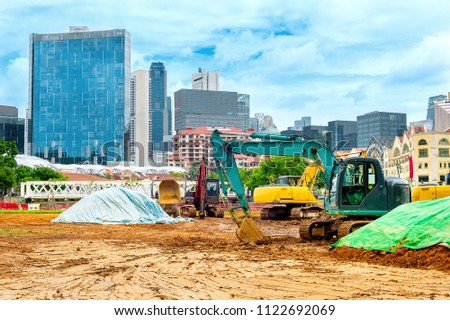 Excavators at construction site in Singapore downtown, modern city skyline on background