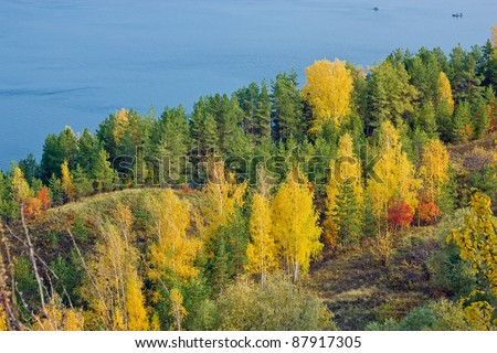 Excellent autumn landscape with yellow, red and green leaves on the trees. The tree line down to the blue river. In the river, the fishermen are fishing from boats.
