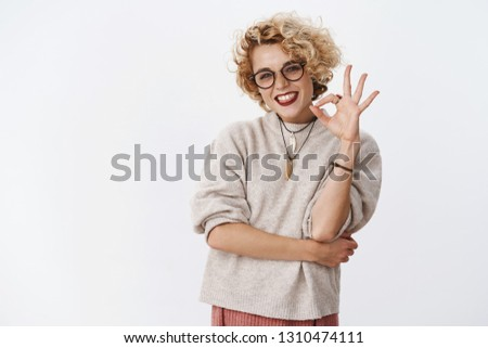 Excellent job, very cool. Portrait of happy and pleased bright charming upbeat woman in glasses and stylish outfit showing okay gesture and smiling delighted and upbeat, having good mood