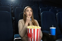 Excellent movie. Young beautiful girl eating popcorn while watching a movie in an empty movie theatre snack holidays entertainment activity alone art enjoy fascination captivating intriguing concept
