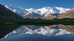 Excellent panoramic view of Lenin Peak massif seen from the Achik-Tash base camp with reflection in the tranquil glacier lagoon, on the border of Kyrgyzstan and Tajikistan, Central Asia.