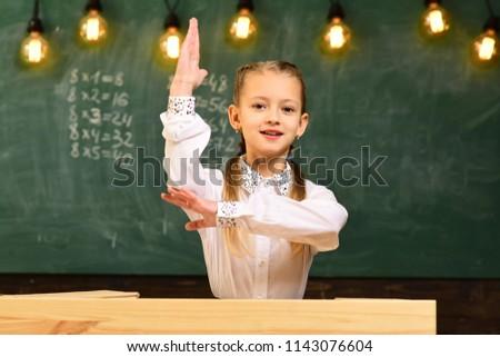 excellent pupil. excellent pupil with raised hand. excellent pupil knows answer. school lesson with excellent pupil #1143076604