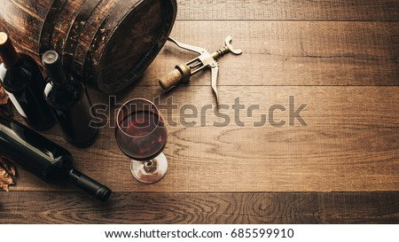 Excellent red wine bottles, wineglass, barrel and corkscrew on a rustic wooden table: traditional winemaking and wine tasting concept #685599910
