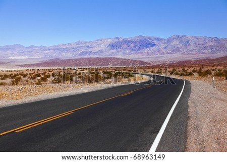 Excellent road, crossing Death Valley in the USA. The low dry bushes and mountains