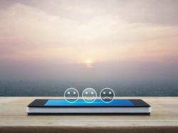 Excellent smiley face rating icon on modern smart mobile phone screen on table over city tower and skyscraper at sunset, vintage style, Customer service evaluation and feedback rating online concept