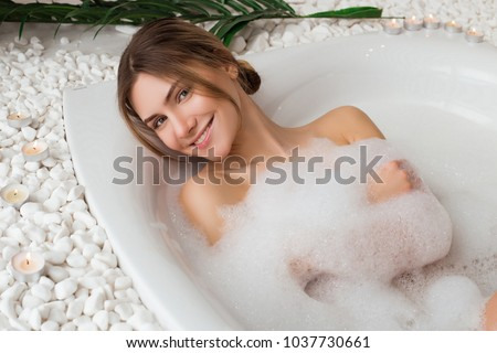 Excelling in care! Tender pretty young model with a charming smile having a soothing bath with foam in the spa salon and posing for camera.