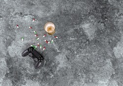 excessive consumption of alcohol, drugs, medicines and computer games damages health, game controller, beer glass and pills on a grey marble table