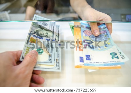 Exchange money, Exchange US dollar or American dollars (USD) for EUR money, A man and women are exchanging dollars for euros.