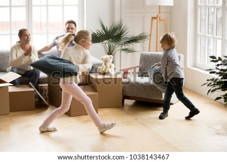 Excited active children having pillow fight on moving day, happy girl and boy playing together in new home while parents laughing supporting kids, family packing boxes or unpacking after relocation