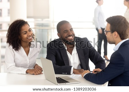 Excited african American couple talk with male realtor or broker consult buying first home together, smiling black husband and wife speak with banker or lawyer discuss taking loan or mortgage