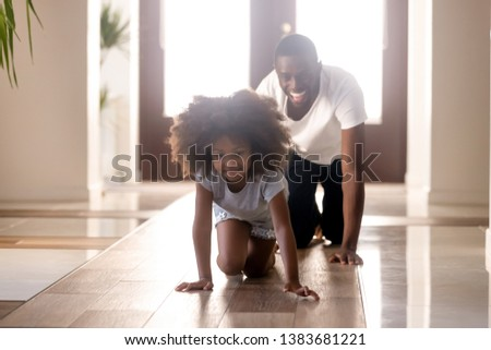 Excited African American dad and small daughter have fun at home grabbling or crawling, happy young black dad play with little kid racing in hallway, smiling funny child enjoy time with parent