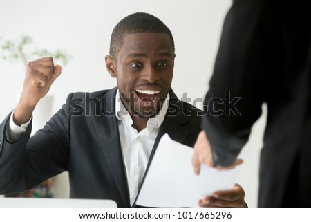 Excited african american employee receives notice about promotion reward achievement at workplace, black entrepreneur celebrates good news about work result or business win success getting new report