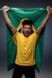 excited african american football fan holding brazilian flag on grey