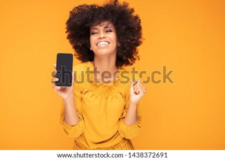 Excited african american girl hold mobile phone with blank empty screen isolated on yellow studio background . Emotions, lifestyle concept. Copy space. Foto d'archivio ©