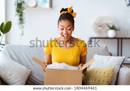 Excited african american girl unboxing cardboard delivery package, sitting at home, copy space