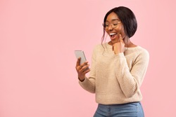 Excited African American Girl Using Smartphone Holding Finger On Chin Standing Over Pink Studio Background. Empty Space