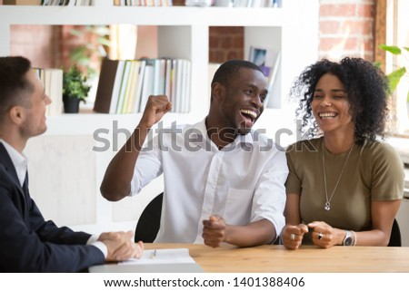 Excited african American husband and wife feel euphoric signing contract buy first house together, overjoyed happy black couple legalize mortgage or loan agreement with broker or realtor in office