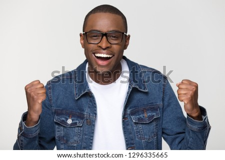 Excited african american man feeling winner triumphant looking at camera isolated on white grey blank studio background, black guy celebrating money win triumph victory success new job opportunity