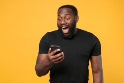 Excited african american man football fan in casual black t-shirt isolated on yellow background studio portrait. People lifestyle concept. Mock up copy space. Using mobile phone typing sms message