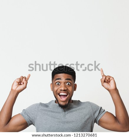Excited african-american man having an idea and pointing two fingers up at copy space, white studio background #1213270681