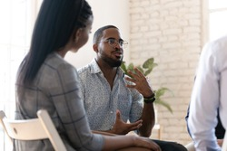 Excited african American man in glasses sit in circle at team therapy session talking sharing thoughts or ideas, motivated biracial male counseling diverse people at group psychotherapy treatment