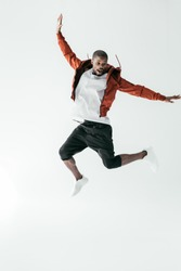 excited african american man jumping in sportswear, isolated on white