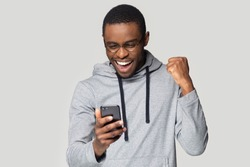 Excited african American millennial male in glasses isolated on grey studio background hold smartphone happy wining online, overjoyed black man look at cellphone smile feel joyful reading good news