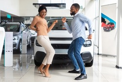 Excited African American Spouses Dancing In Dealership Office After Buying New Car, Cheerful Black Couple Having Fun In Auto Showroom, Celebrating Purchasing Family Automobile, Free Space