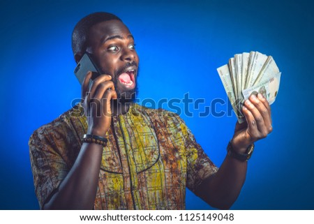Excited african-american winner with money and phone