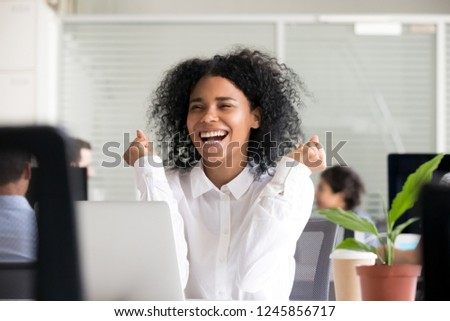 Excited African American woman receiving good news in email on laptop, motivated black female employee getting promoted, celebrating business achievement, reward, great results, win, opportunity
