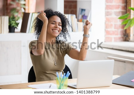 Excited african American woman sit at desk feel euphoric win online lottery, happy black woman overjoyed get mail at laptop being promoted at work, biracial girl amazed read good news at computer
