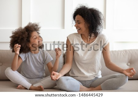 Excited african american woman teaching cute little adorable daughter meditating and practicing yoga exercises. Happy mixed race family sitting on comfy couch in lotus position, having fun together. Photo stock ©