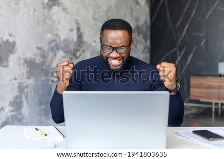 Excited African-American young businessman screams yes, sitting at the desk with a laptop in modern office, overjoyed black office employee rejoys job offer, clenched fists in triumph Photo stock ©