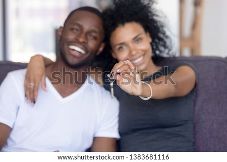 Excited African American young family show keys to own home, happy black couple sit on couch praise buying first house together, smiling husband and wife purchase new property. Ownership concept