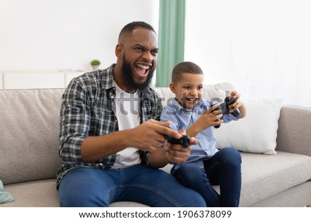 Excited African Dad And Son Playing Game Having Fun Sitting On Couch At Home. Young Black Father And His Kid Play Videogames Spending Time Together On Weekend Concept