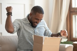 Excited african man customer receive good parcel open cardboard box at home satisfied with great purchase, happy black male consumer unpack package look inside overjoyed by postal shipping delivery