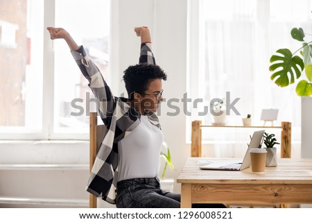 Excited african teen girl receiving good news in email about online win, great test exam results or college admission, victory success feeling motivated looking at laptop get hired new job opportunity