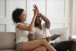 Excited african wife gives high five husband holding tablet computer, young couple celebrating fantastic received opportunity, bank approve loan e-mail, booked hotel for future vacation travel concept