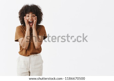 Excited amazed attractive african american young woman with afro hairstyle tilting towards camera screaming and holding hands on face being thrilled and enthusiastic during favorite band perfomance