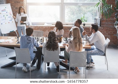 Excited asian girl making business presentation for international team of colleagues, office interior