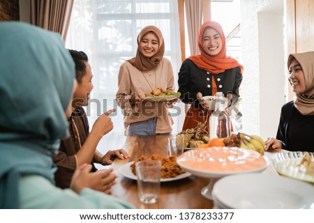 excited asian muslim people served with food for lunch during eid mubarak celebration
