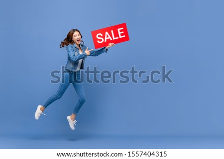 Excited Asian woman in casual jean clothes jumping with red sale sign in hand isolated on light blue background with copy space