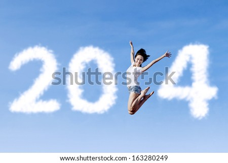Excited asian woman is jumping with new year 2014 on the clear sky