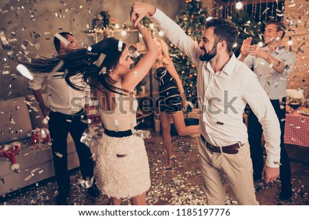 Excited attractive charming beautiful cheerful well-dressed couple, husband spinning elegant alluring wife, ladies and handsome gentlemen at home festive, chill out, glitter falling down around