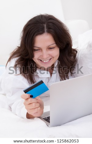 Excited attractive young woman lying on her bed with her laptop making purchases online with her credit card