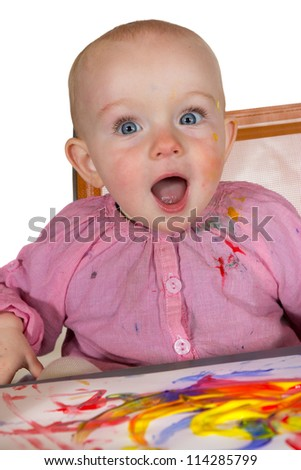 Excited baby girl painter with her eyes and mouth open wide in wonderment at the colorful artwork she has created with a rainbow of colours