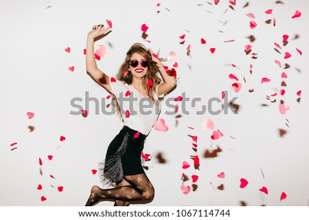 Excited barefooted girl jumping under heart confetti. Slim young woman in pantyhose expressing energy during dance in studio.