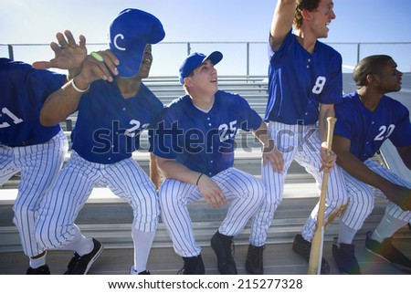 Excited baseball team jumping up from bench in stand during competitive baseball game, cheering, front view (backlit)
