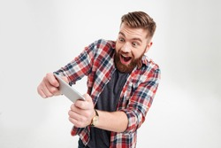 Excited bearded man in plaid shirt playing on smartphone over white background