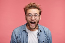 Excited bearded man wears glasses and denim shirt watches football match with friends, being great fan, involved in game, screams happily because of scored goal, rejoice team`s victory and success
